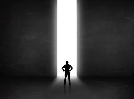 tunnel di luce: Persona di affari che esamina parete con tunnel di luce il concetto di apertura