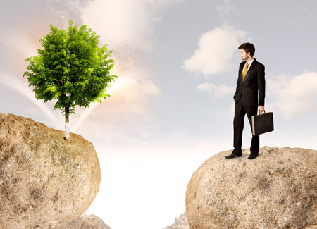 bridging the gaps: Businessman standing on the edge of rock mountain with a tree on the other side Stock Photo