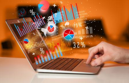 Hand te typen op een moderne laptop notebook computer met toekomstige grafiek pictogrammen en symbolen Stockfoto