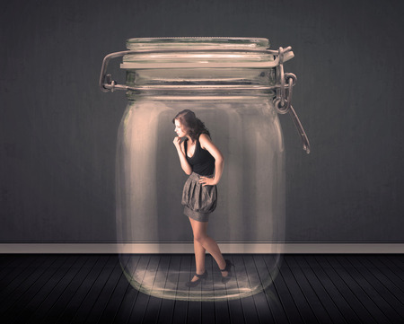 are trapped: Businesswoman trapped into a glass jar concept on background Stock Photo