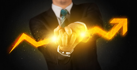 rise rising: Business person holding a hot glowing upright arrow concept on background