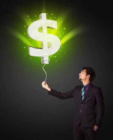 dreamer: Businessman holding a shining, green dollar sign balloon
