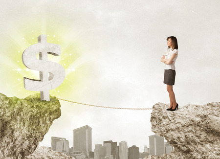 bridging the gaps: Businesswoman standing on the edge of mountain with a shining dollar mark on the other side
