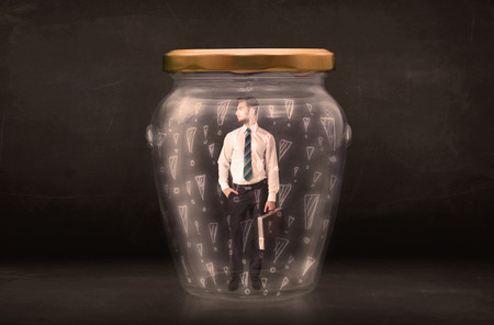 are trapped: Business man trapped in jar with exclamation marks concept on bakcground