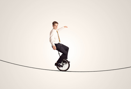 Extreme business man riding unicycle on a rope concept on background photo