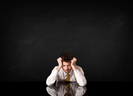 worried businessman: Depressed businessman sitting at a desk