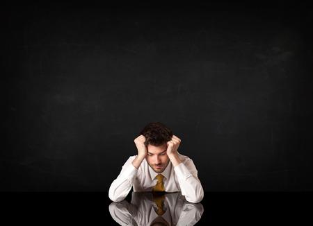 decepcionado: Hombre de negocios deprimido sentado en un escritorio