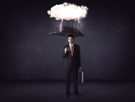 Businessman standing with umbrella and little storm cloud concept on background photo