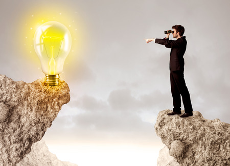 other side: Businessman standing on the edge of mountain with an idea bulb on the other side