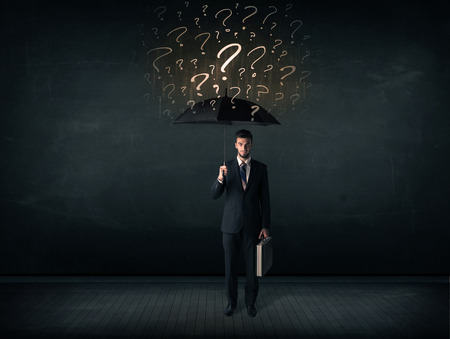 Businessman with umbrella and a lot of drawn question marks concept on background photo