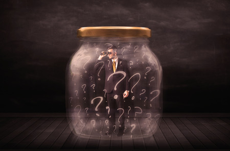 claustrophobia: Businessman locked into a jar with question marks concept on background Stock Photo