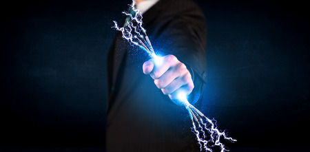 Business person holding electrical powered wires concept on background photo