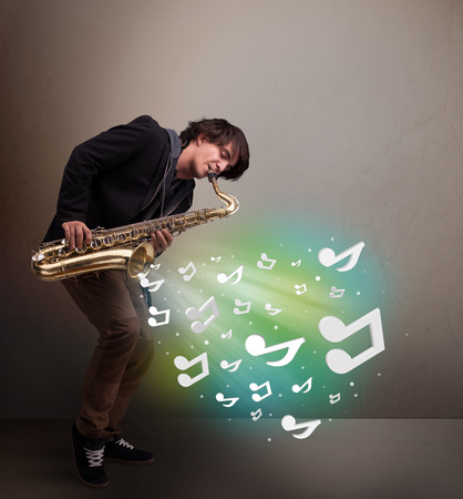 Attractive young musician playing on saxophone while musical notes exploding photo