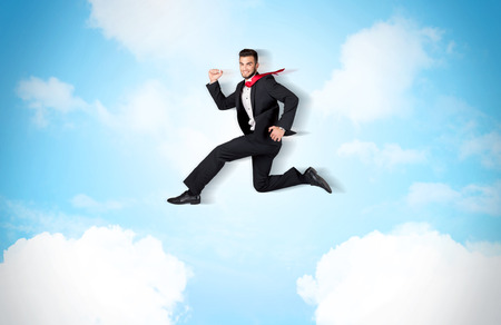 Business person jumping over clouds in the blue sky concept photo