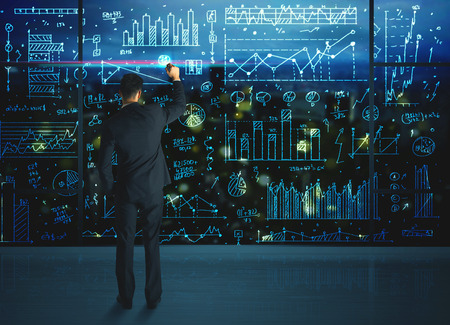 Businessman drawing business statistics on glass wall photo