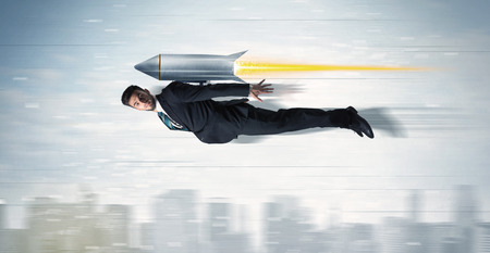 man flying: Superhero business man flying with jet pack rocket above the city concept Stock Photo