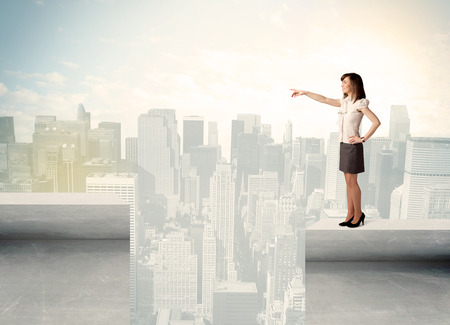 bridging the gap: Businesswoman standing on the edge of rooftop with city background