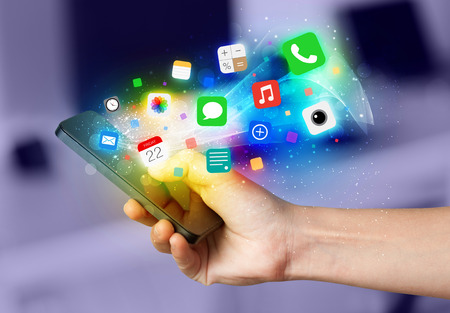Hand holding smartphone with colorful app icons concept photo