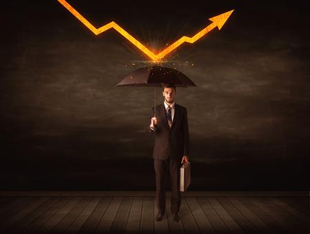 Businessman standing with umbrella keeping orange arrow concept on background Imagens