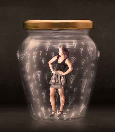 trapped: Business woman trapped in jar with exclamation marks concept on bakcground