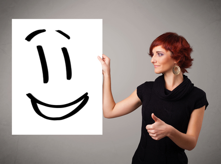 Attractive young woman holding smiley face drawing photo