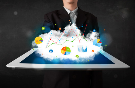 Person holding a white touchpad with cloud technology and charts photo