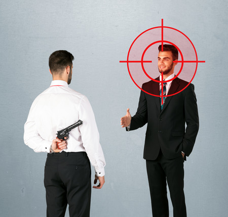 hidden danger: Ruthless businessman handshake with a hiding weapon and a head target point