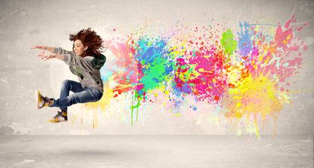 Boldog tinédzser ugrás színes tintával fröccs városi háttér koncepció
