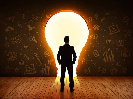 leadership key: Business man looking at bright light bulb in the wall concept Stock Photo