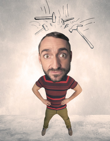 gladness: Funny person with big head and drawn punching hammers over it Stock Photo