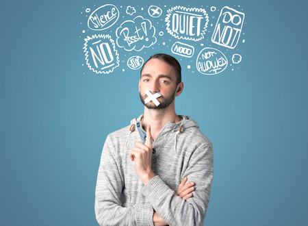 thought clouds: Young man with taped mouth and white drawn thought clouds around his head
