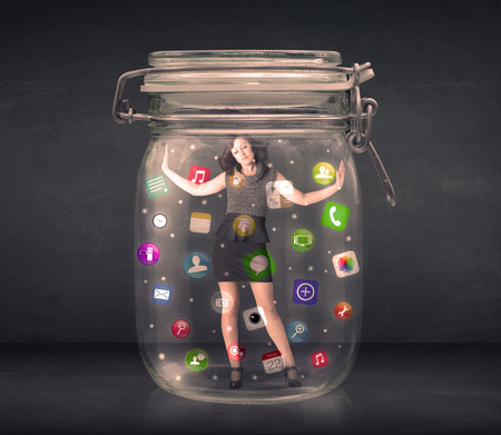 captured: Businesswoman captured in a glass jar with colourful app icons concept on background Stock Photo