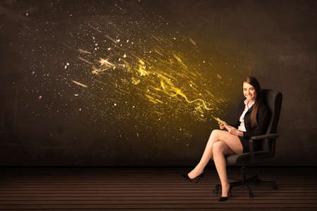 Businesswoman with tablet and energy explosion on background concept photo