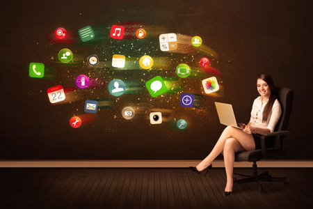 Business woman sitting in office chair with laptop and colorful app icons concept on background photo