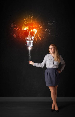 Businesswoman with an explosion bulb on black background photo
