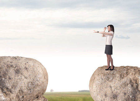 bridging the gaps: Young businesswoman standing on edge of rock mountain