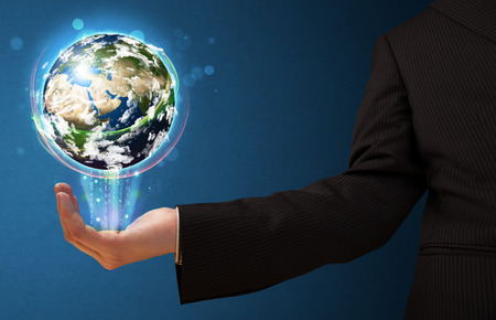 businessman carrying a globe: Young businessman holding in his hand a glowing earth globe, Elements of this image furnished by NASA