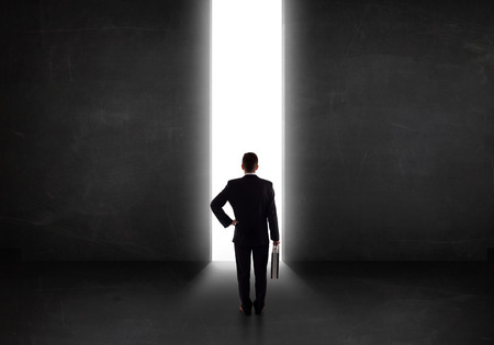 light tunnel: Business person looking at wall with light tunnel opening concept