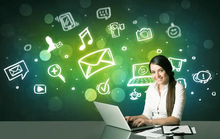 trabajo social: Empresaria que se sienta en la mesa de negro con símbolos de medios sociales en el fondo