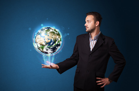 businessman carrying a globe: Young businessman holding in his hand a glowing earth globe Stock Photo