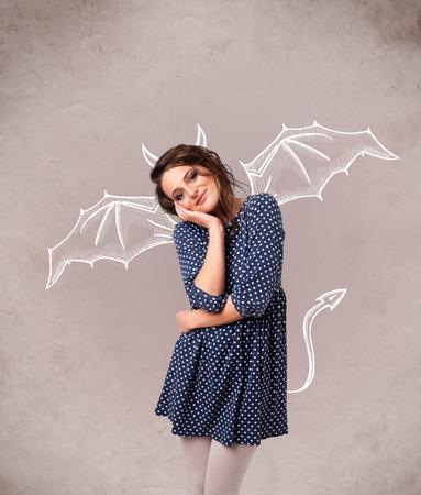 Giovane ragazza brutta con corna da diavolo e le ali di disegno