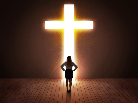 Woman looking at bright cross sign concept