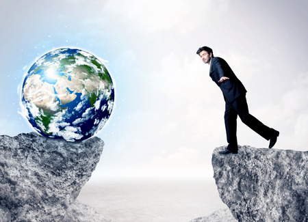 bridging the gap: Businessman standing on the edge of mountain with a globe on the other side Stock Photo
