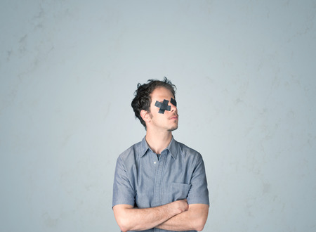 dismay: Young man with taped eye. Isolated on gray background