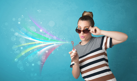 Beautiful girl blowing abstract colorful bubbles and lines on blue background photo