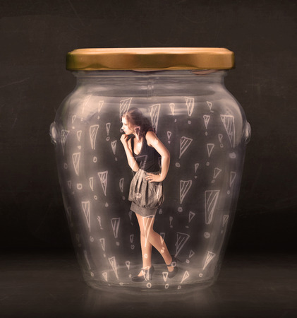 are trapped: Business woman trapped in jar with exclamation marks concept on bakcground