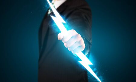 Business man holding glowing lightning bolt in his hands concept Stock Photo
