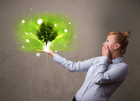 Young businesswoman holding a glowing tree in her hand photo