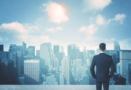BUSINESSMEN: Businessman standing on a roof and looking at future city Stock Photo