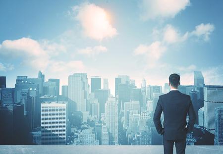 traje: Empresario de pie sobre un techo y mirando a futuro de la ciudad Foto de archivo